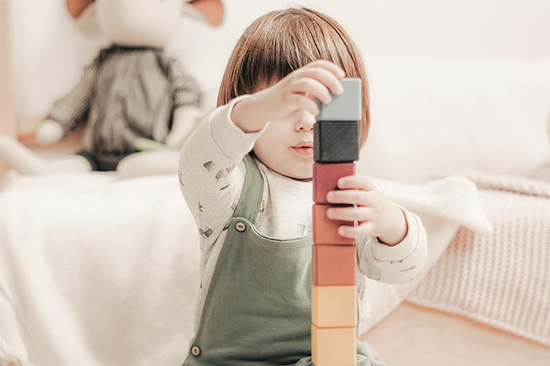 child playing with wooden blocks
