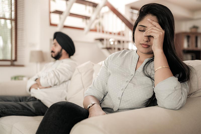 indian couple sitting apart on lounge looking unhappy with each other
