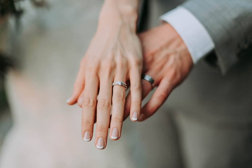woman's hand on top of man's - both are wearing their wedding rings indicating marriage
