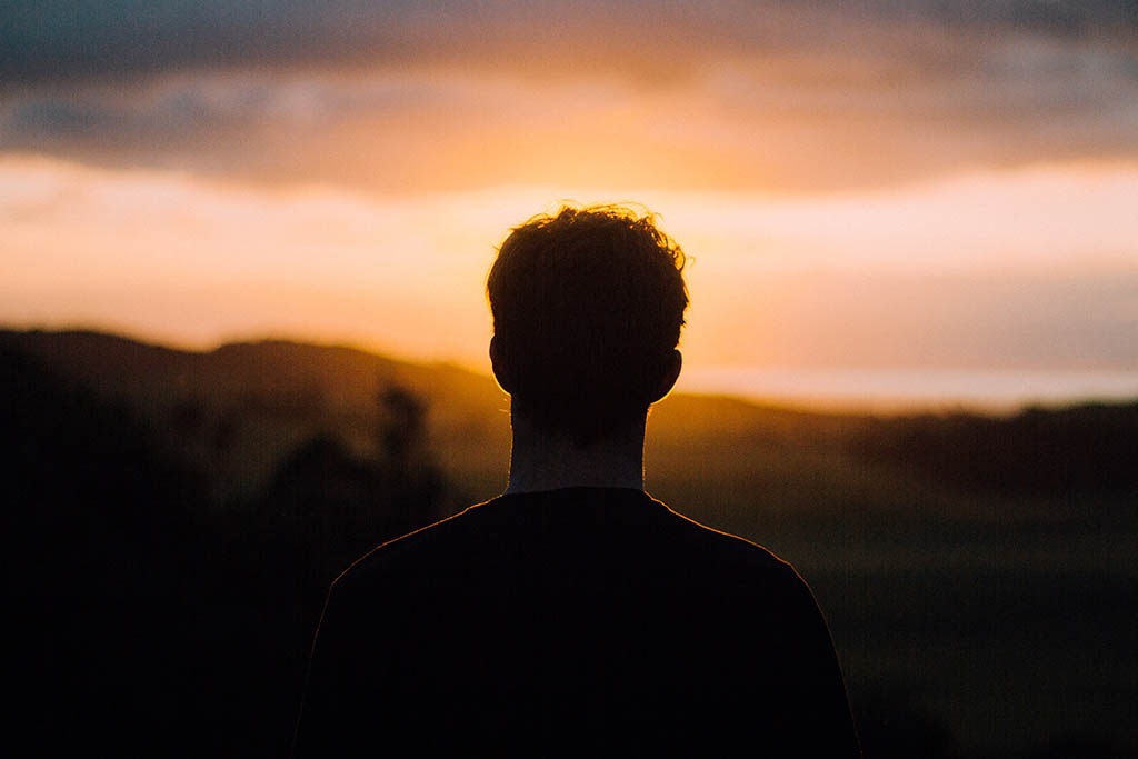 silhouette of a man's back as he looks into a the horizon at sunset